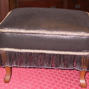 Faux-suede, chenille welt and a fine slurry transform this ottoman. Note That the string had not been removed to free the fringe yet