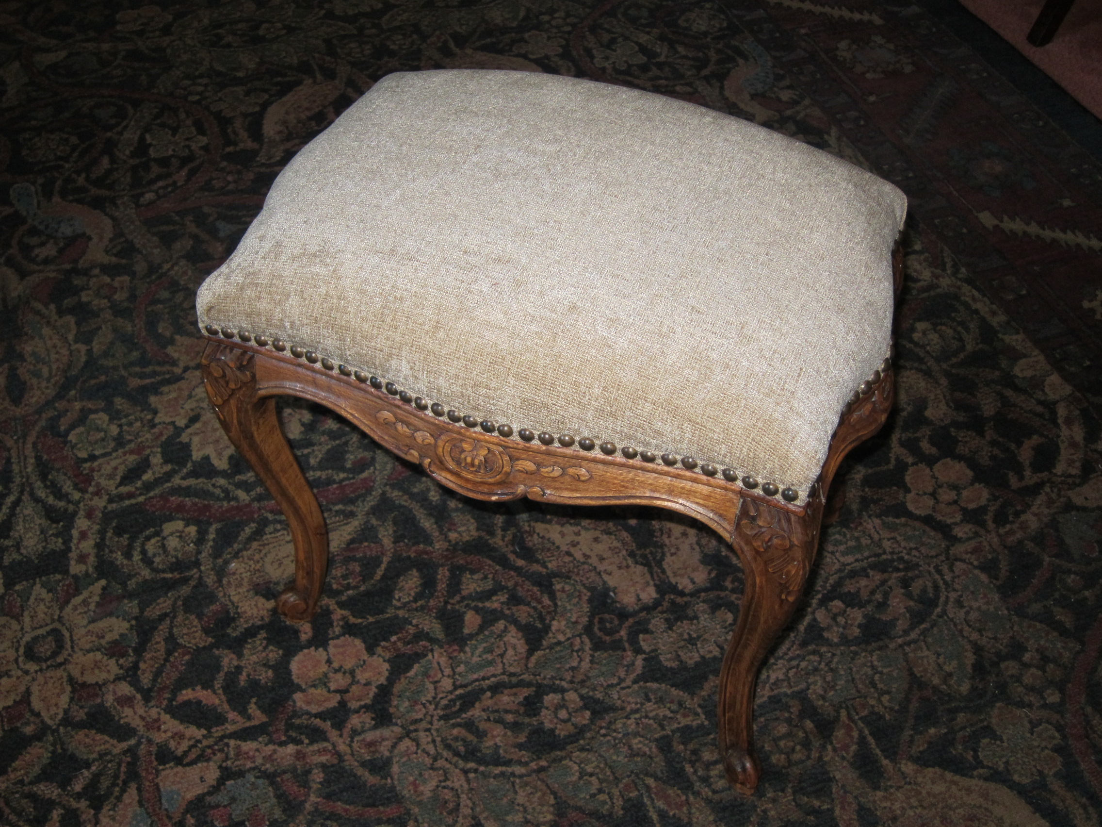 A clean new cover and hobnails update this carved ottoman